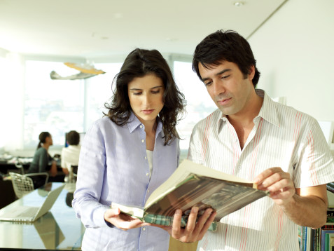 Man and woman seeing a book together at the office